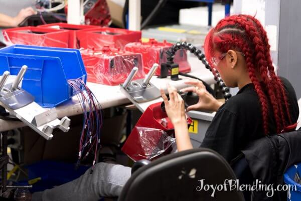 Vitamix factory worker installing faceplates